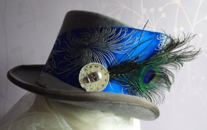 China Blue...Grey top hat, with peacock feathers, a aged clock face and that jaunty little skull to keep them all guessing if your naughty or nice!